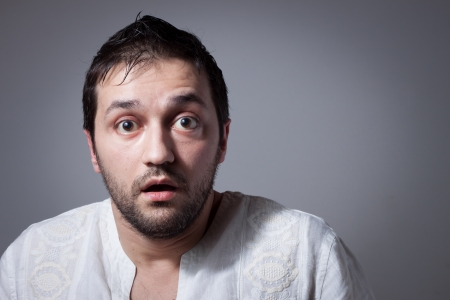 Young bearded man with astonished expression on dark background Stock Photo
