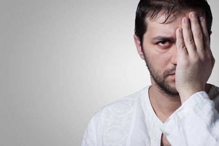 Young bearded man with his hand covering an eye on grey background