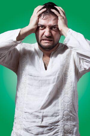 anguished: Divertente uomo barbuto con disperata espressione su sfondo verde