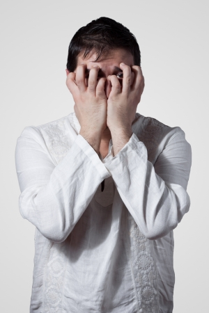 anguished: Young man hiding his face with hands while looking through fingers