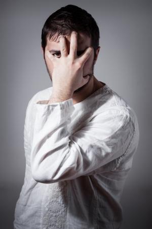 anguished: Giovane uomo nascondendo il viso con una mano, mentre guardando attraverso le dita