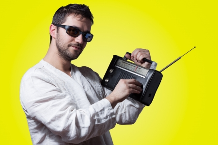 tune: Young bearded man holding a vintage radio on yellow background