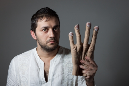 Young bearded man with interrogative expression on his face holding a huge mock hand