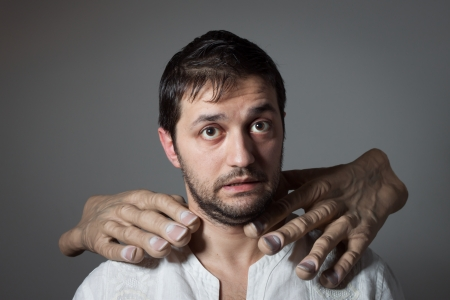 Young bearded man choked by two huge hands on dark background