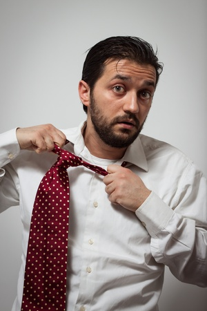 Young bearded man removing his red tie