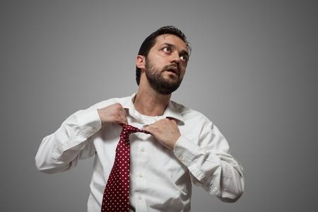 suffocating: Giovane uomo con la barba rimuovere la sua cravatta rossa su sfondo grigio Archivio Fotografico