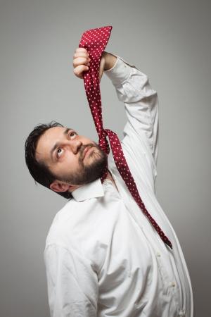 suffocating: Giovane uomo con la barba finta di impiccarsi con una cravatta rossa