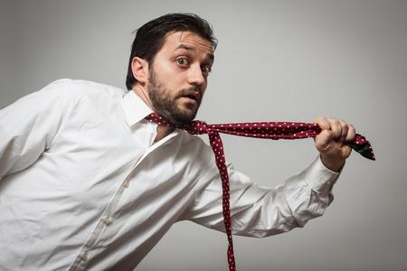 suffocating: Giovane uomo barbuto con cravatta rossa che si tira su sfondo grigio