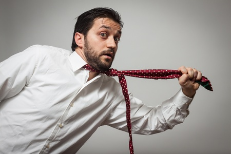 suffocating: Young bearded man with red tie pulling himself on grey background