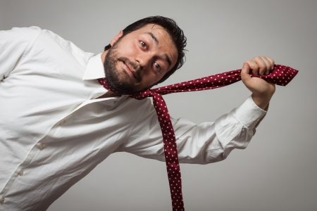 Young bearded man with red tie pulling himself on grey background