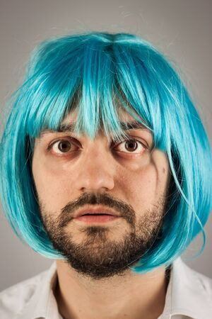 Funny bearded man with a blue wig on grey background photo