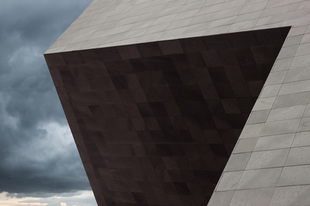 Architectural detail of a modern building with dramatic sky