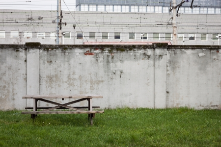 Table and bench in the grass close to a grey wall limiting the railroad