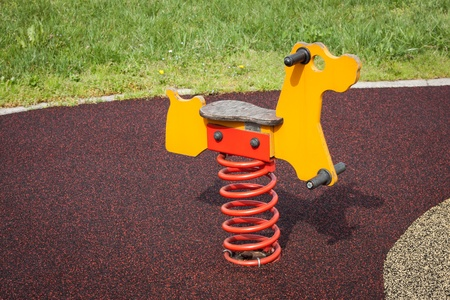Modern rocking horse in a city park playground photo