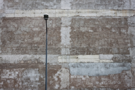 squalid: Lamppost with a coarse concrete wall on background