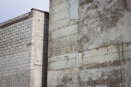 squalid: Coarse concrete walls with a narrow passage in the middle Stock Photo