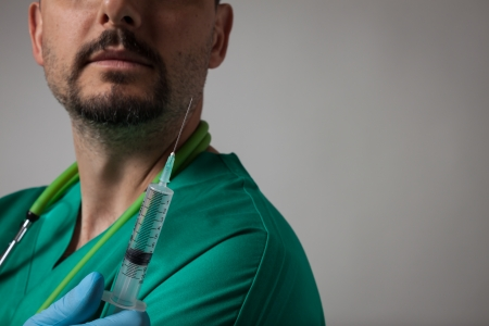 Portrait of a young physician with green uniform holding syringe photo