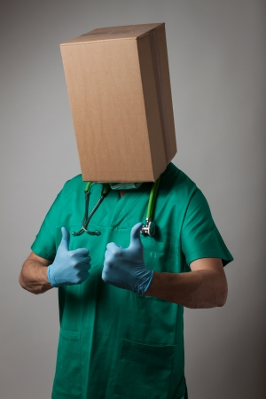 Doctor with cardboard box head in green uniform