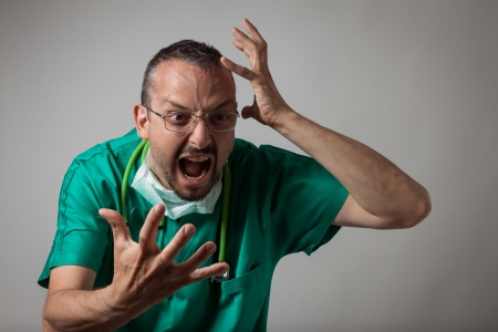 nurse gloves: Portrait of a young physician shouting in green uniform Stock Photo