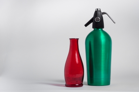 seltzer: Still life of red bottle and green seltzer siphon on grey background Stock Photo