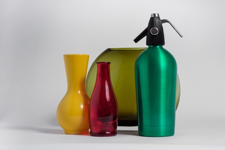 seltzer: Still life of red bottle yellow vase and green seltzer siphon on grey background