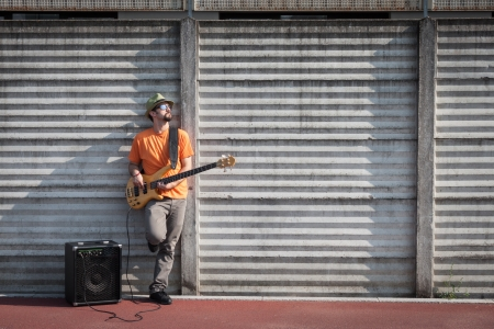 Young musician playing bass guitar in the street photo