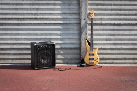 Bass guitar and amplifier against a concrete wall
