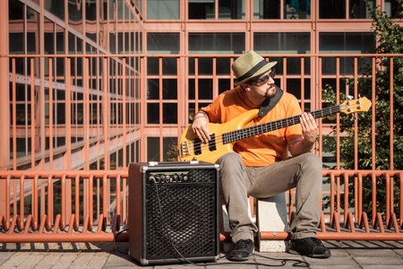 bassist: Young musician with hat playing bass guitar Stock Photo
