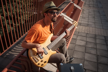 Young musician with hat playing bass guitar photo