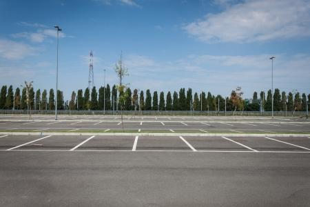 Lege parkeerplaats met bomen in de verte Stockfoto