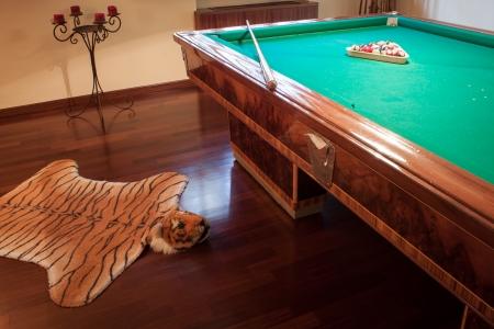 Billiard table with mock tiger skin rug on parquet floor photo