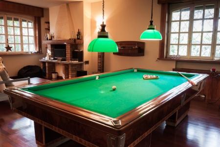 snooker room: Billiard table with mock tiger skin rug on parquet floor Stock Photo