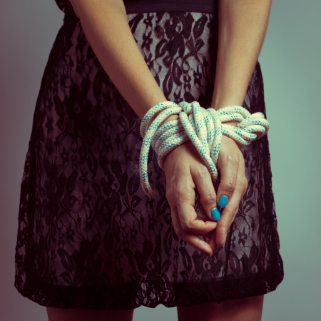 Detail of female hands tied up with rope photo
