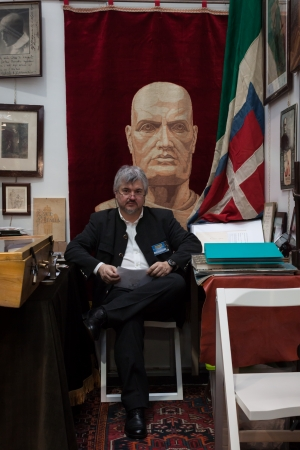MILAN, ITALY - NOVEMBER 2  An exhibitor sits in his stand at Militalia, exhibition dedicated to militaria collectors and military associations on NOVEMBER 2, 2013 in Milan