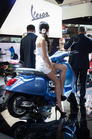 primavera: MILAN, ITALY - NOVEMBER 5  Beautiful model poses on the new Vespa Primavera at EICMA, international motorcycle exhibition on NOVEMBER 5, 2013 in Milan