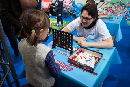come in: MILAN, ITALY - NOVEMBER 22  Young girl plays Connect Four at G  come giocare, trade fair dedicated to games, toys and children on NOVEMBER 22, 2013 in Milan