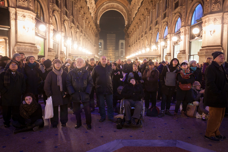 MILAN, ITALY - DECEMBER 7  People look at the screen broadcasting Verdi