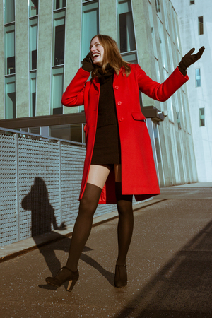 Beautiful girl with red coat talking on phone in the street photo