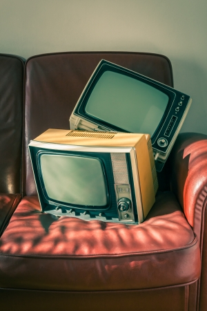 Two portable vintage televisions on red couch Stock Photo
