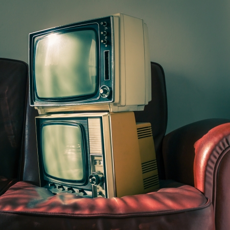 Two portable vintage televisions on red couch photo