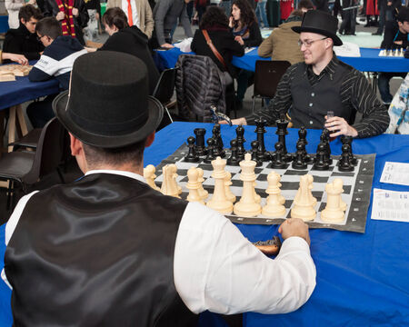 MILAN, ITALY - FEBRUARY 2: Two guys play chess at Festival del Fumetto, convention dedicated to comics and cosplay world on FEBRUARY 2, 2014 in Milan.