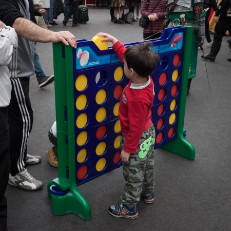 MILAN, ITALY - FEBRUARY 2: Young boy plays connect 4 at Festival del Fumetto, convention dedicated to comics and cosplay world on FEBRUARY 2, 2014 in Milan.