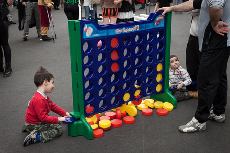 MILAN, ITALY - FEBRUARY 2: Young boys play connect 4 at Festival del Fumetto, convention dedicated to comics and cosplay world on FEBRUARY 2, 2014 in Milan.