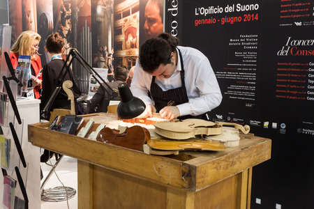 reference point: MILAN, ITALY - FEBRUARY 13  Luthier works on a violin at Bit, international tourism exchange reference point for the travel industry on FEBRUARY 13, 2014 in Milan  Editorial
