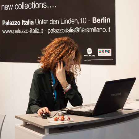 reference point: MILAN, ITALY - FEBRUARY 13  Beautiful hostess working at computer at Bit, international tourism exchange reference point for the travel industry on FEBRUARY 13, 2014 in Milan  Editorial
