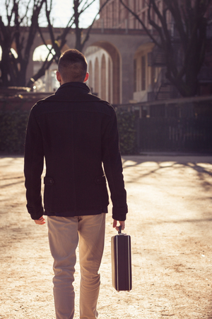 Handsome young man walking alone with a briefcase photo
