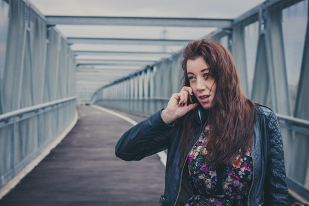 Pretty girl with long hair and black leather jacket talking on phone  photo