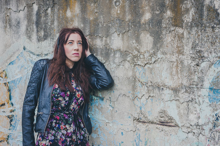 Pretty girl with long hair and black leather jacket leaning against a concrete wall photo