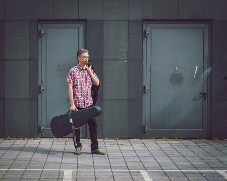 guitar case: Hombre en la camisa de manga corta de la celebraci�n de caja de la guitarra en la calle