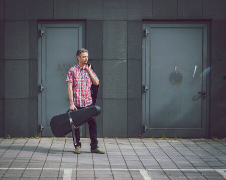 guitar case: Man in short sleeve shirt holding guitar case in the street Stock Photo